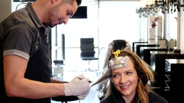 happy mid adult woman smiles as she talks with hair stylist - stile di capelli video stock e b–roll