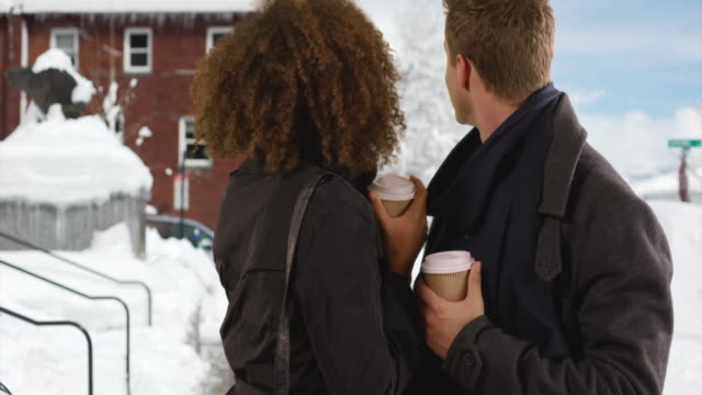 happy millennial couple drink coffee outside in the snow - coffee drink stock videos and b-roll footage