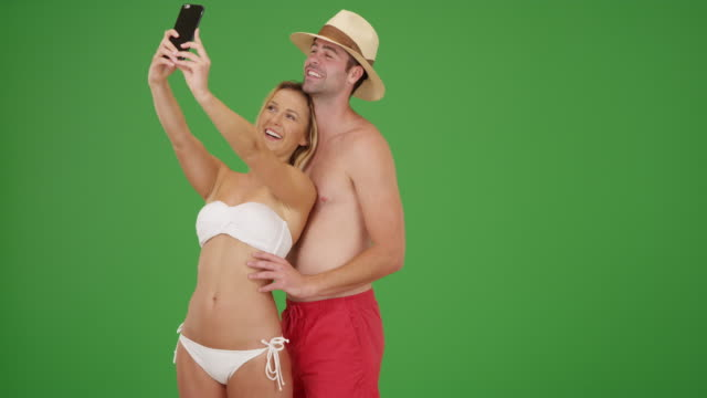 happy millennial couple taking selfies by the beach on green screen - standing stock videos & royalty-free footage