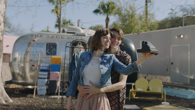 happy millennial hipster couple take a polaroid selfie while trying on boho clothing from a mobile fashion truck - polaroid camera stock videos & royalty-free footage