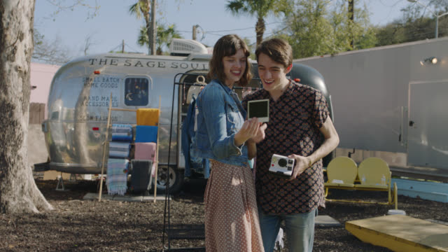 happy millennial hipster couple take polaroids while trying on boho clothing from a mobile fashion truck - shaking stock-videos und b-roll-filmmaterial
