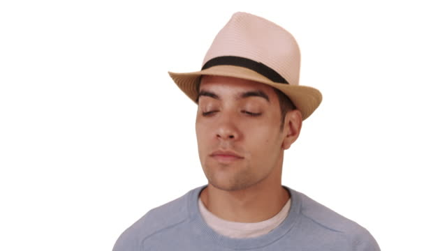 happy millennial hispanic mixed race man standing on white background with hat - solid stock videos and b-roll footage