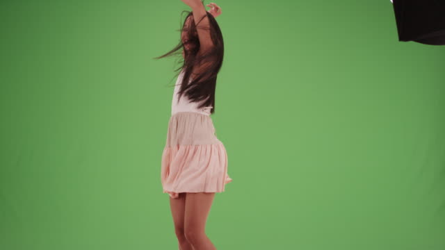 Happy millennial Latina dancing around in a dress on green screen
