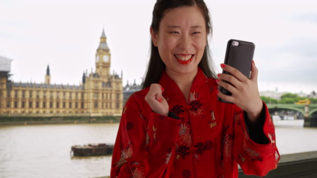happy millennial woman taking selfie with smartphone in london uk - big ben点の映像素材/bロール