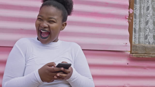 Happy millennial young African woman excited about a message in the mobile phone