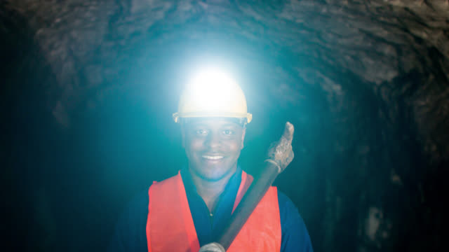 happy miner working at a mine underground - minatore video stock e b–roll