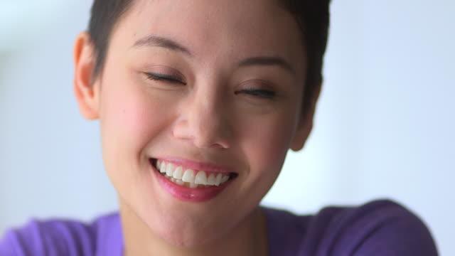 stockvideo's en b-roll-footage met happy mixed race asian woman smiling - natuurlijk haar