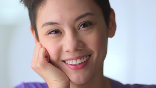 stockvideo's en b-roll-footage met happy mixed race asian woman with hand on cheek - natuurlijk haar