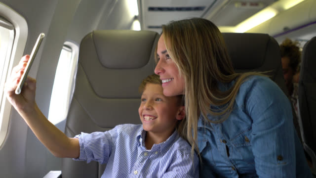 happy mom and son taking a selfie during the air flight - passenger stock videos & royalty-free footage