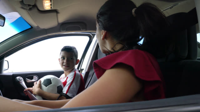 happy mom picking up her son after soccer practice in car - drive ball sports stock videos & royalty-free footage