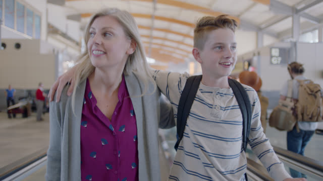 vídeos de stock, filmes e b-roll de happy mother and adolescent son stand on moving walkway in airport terminal. - adolescência
