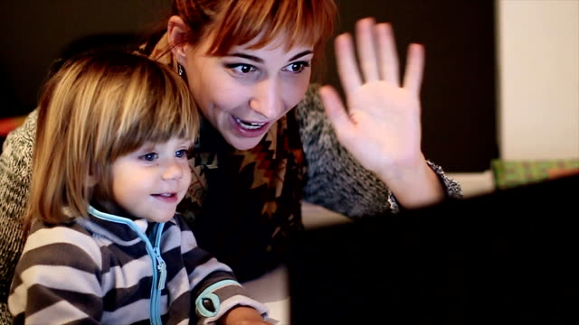 happy mother and baby son using laptop in the living room - voip stock videos & royalty-free footage