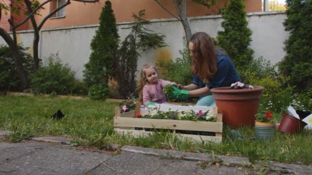 vidéos et rushes de mère et descendant heureux appréciant tout en jardinant ensemble - gant de jardinage