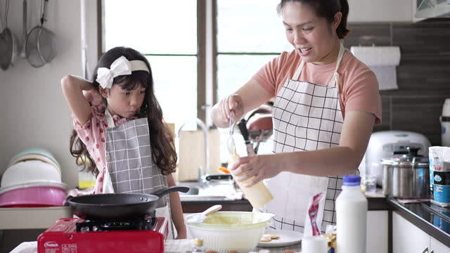 stockvideo's en b-roll-footage met happy mother and daughter making a pan cake in kitchen at home - driekwartlengte