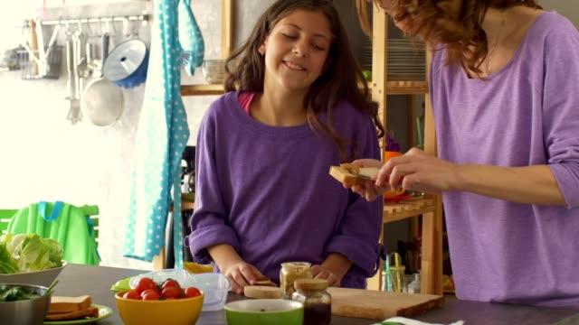 ピーナッツバターサンドイッチを作る幸せな母と娘 - サンドイッチ作り点の映像素材/bロール