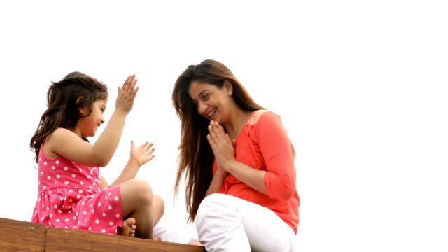 MS Happy mother and daughter playing patty cake on wooden jetty over lake / India