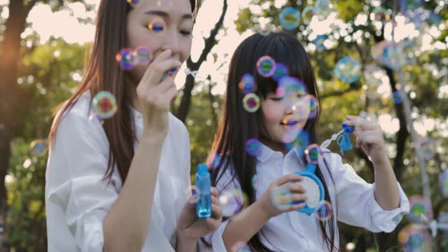 happy mother and daughter playing together outdoor, blowing soap bubbles, having fun in the park.little girl and mother playing with bubbles in the park on a sunny day.family, mother's day.relaxed parenting - mother's day stock videos & royalty-free footage