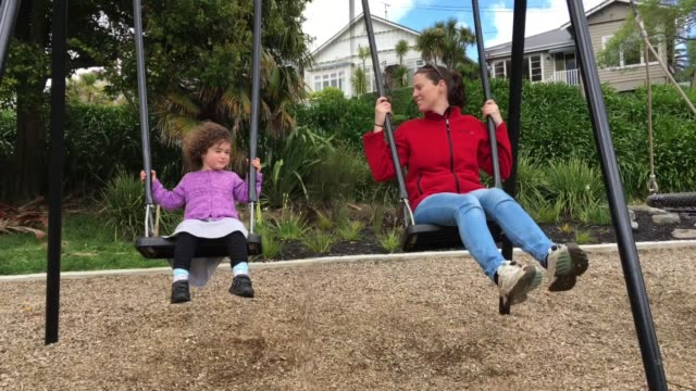 Happy mother and daughter swinging on a swing together