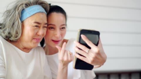 vídeos de stock, filmes e b-roll de mãe e filha felizes tirando foto de selfie com câmera de smartphone. - avós e avôs
