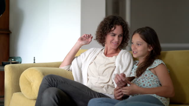 vidéos et rushes de happy mother and daughter talking on sofa at home - chatouiller