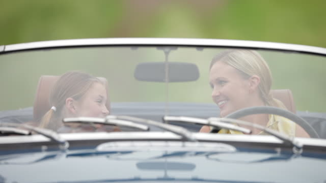 Happy mother and daughter talking with sitting in convertible