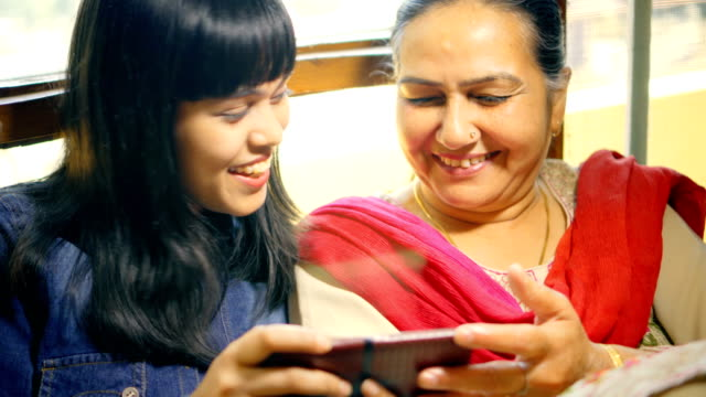 happy mother and daughter use and share a smartphone together. - close to stock videos & royalty-free footage