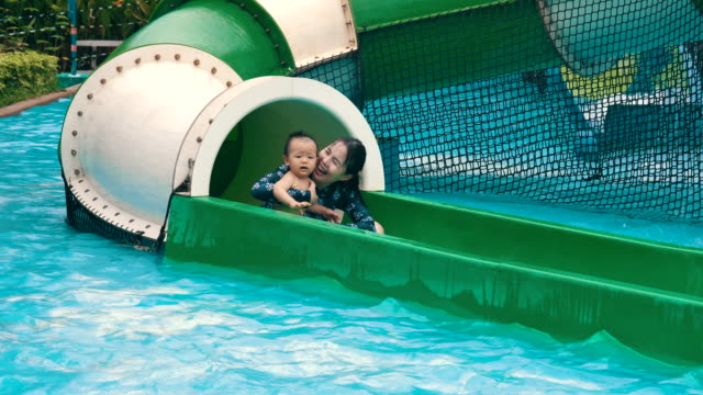 happy mother and her baby boy sliding on water slide - 6 11 months stock videos & royalty-free footage