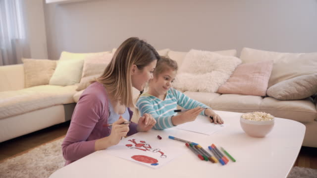 Happy mother and her daughter having fun while coloring at home.