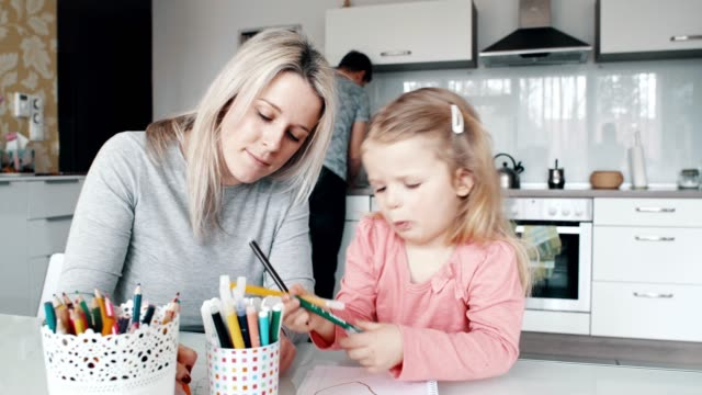 happy mother and her daughter having fun while drawing, father is washing dishes - guru stock videos & royalty-free footage