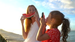 Happy mother and her daughter sitting on a wooden pier and eating a juicy watermelon