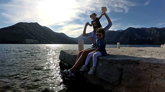 happy mother and her daughters sitting on pier slow motion - perast stock videos and b-roll footage