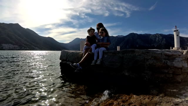 happy mother and her daughters sitting on pier - perast stock videos and b-roll footage