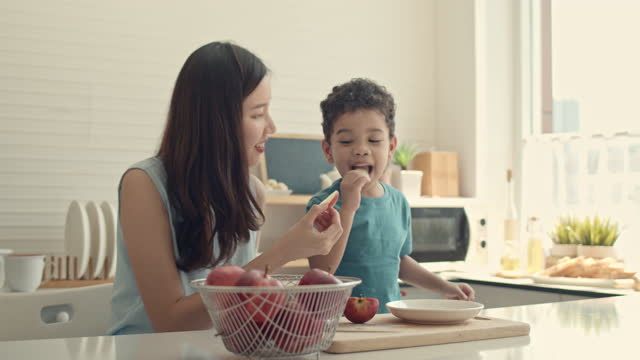 happy mother and her son eating apples in the kitchen - freshness stock videos & royalty-free footage