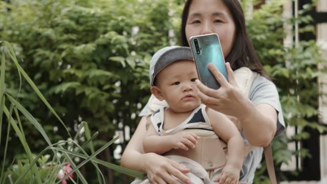 vídeos de stock, filmes e b-roll de mãe e menino feliz tirando foto de selfie com smartphone - 6 11 months
