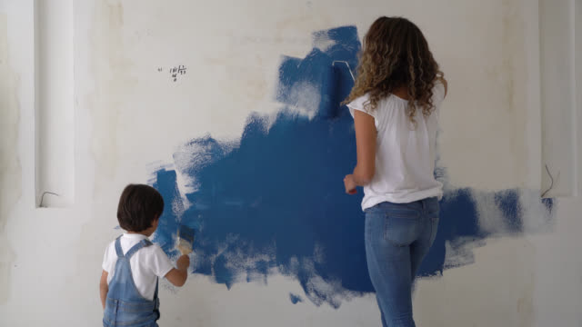 happy mother and son having fun painting a wall at home - painting stock videos & royalty-free footage
