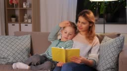 happy mother and son reading book sofa at home