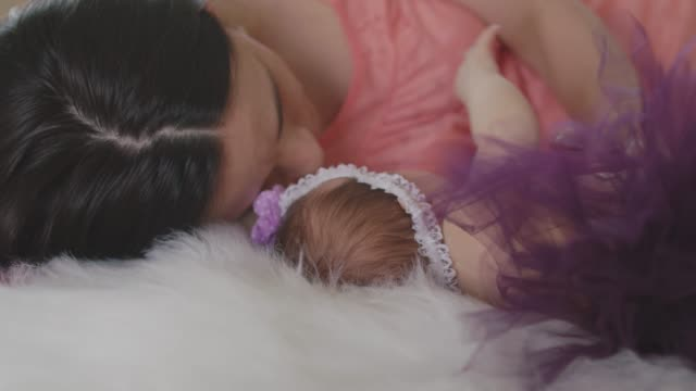happy mother cuddling her little newborn baby girl on bed - tutu stock videos & royalty-free footage