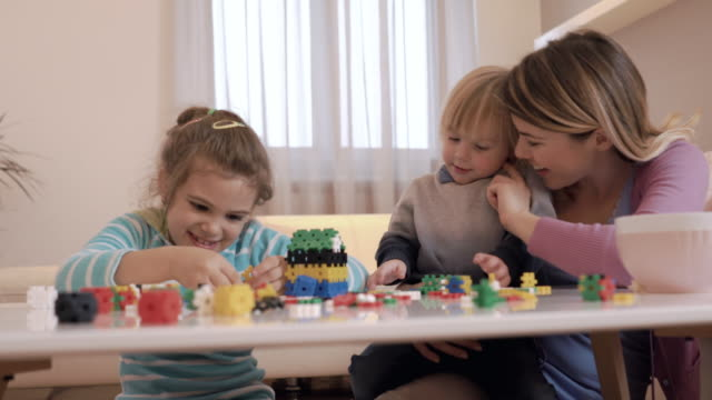 happy mother enjoying with her kids while playing with puzzles. - family with two children stock videos & royalty-free footage