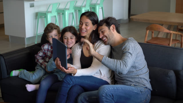 happy mother holding a tablet while everyone waves hi during a video call with someone all smiling - video call stock videos & royalty-free footage