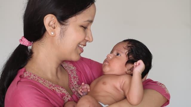 Happy mother holding newborn baby boy