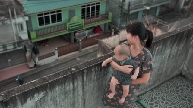 vídeos de stock e filmes b-roll de happy mother is comforting her child on rooftop - carregar uma pessoa nos ombros