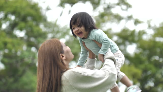 happy mother throwing baby girl in park - two generation family stock videos & royalty-free footage