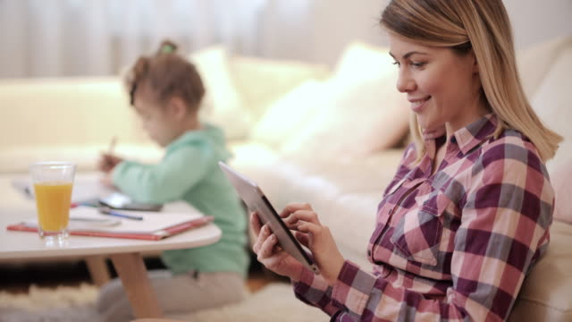 happy mother using digital tablet at home while her daughter is coloring in the background. - touchpad stock videos & royalty-free footage