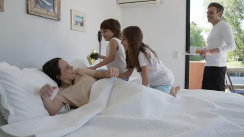 vídeos y material grabado en eventos de stock de feliz madre despertando emocionada con un regalo y desayuno en la cama para el día de la madre - desayuno