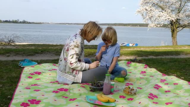 glückliche mutter mit sohn machen picknick am see - decke bettwäsche stock-videos und b-roll-filmmaterial
