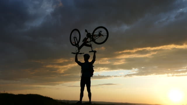 4К Happy mountain biker picking up his bike on top mountain