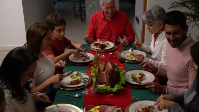 happy multi generational family enjoying their christmas dinner eating while talking and smiling - christmas meal stock videos & royalty-free footage