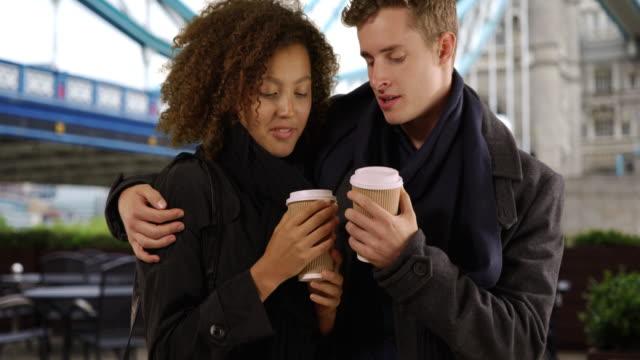 happy multiethnic couple drink coffee near tower bridge - coffee drink stock videos & royalty-free footage