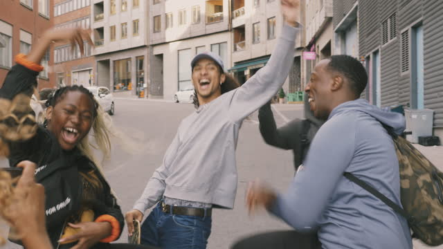 happy multi-ethnic friends dancing on street in city - real time footage stock videos & royalty-free footage