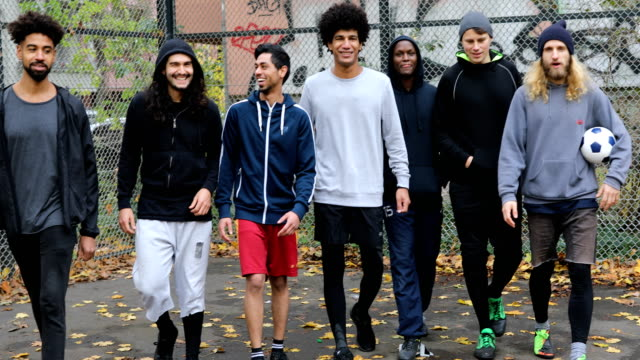 happy multi-ethnic soccer team walking with ball - football team stock videos & royalty-free footage